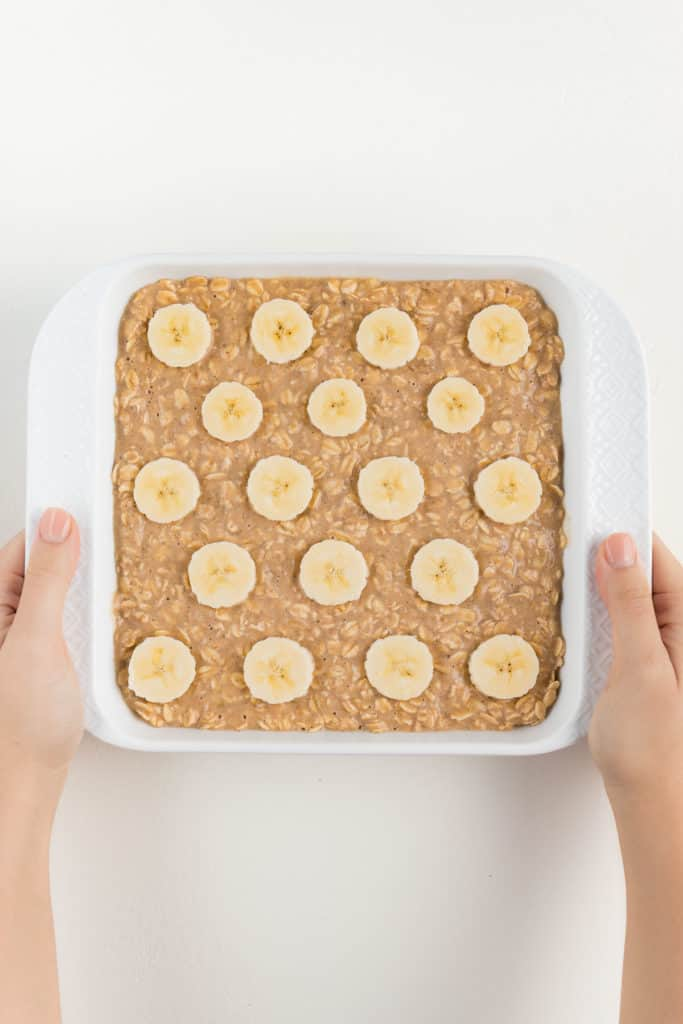 two hands holding a white square baking dish that contains oatmeal batter with bananas