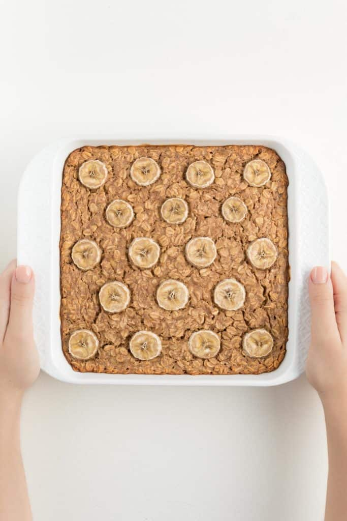 two hands holding a white square baking dish that contains baked banana oatmeal