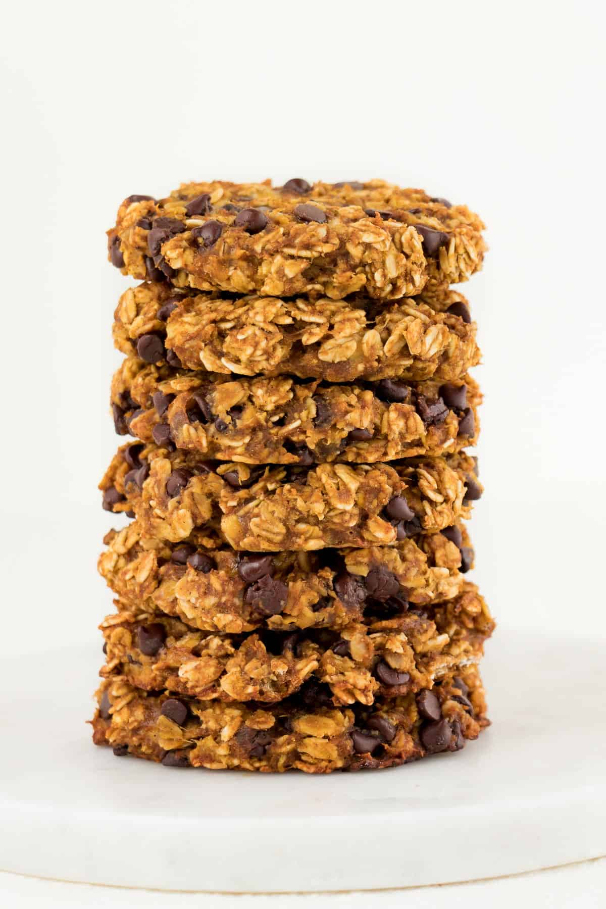 seven oatmeal chocolate chip pumpkin cookies stacked on top of each other