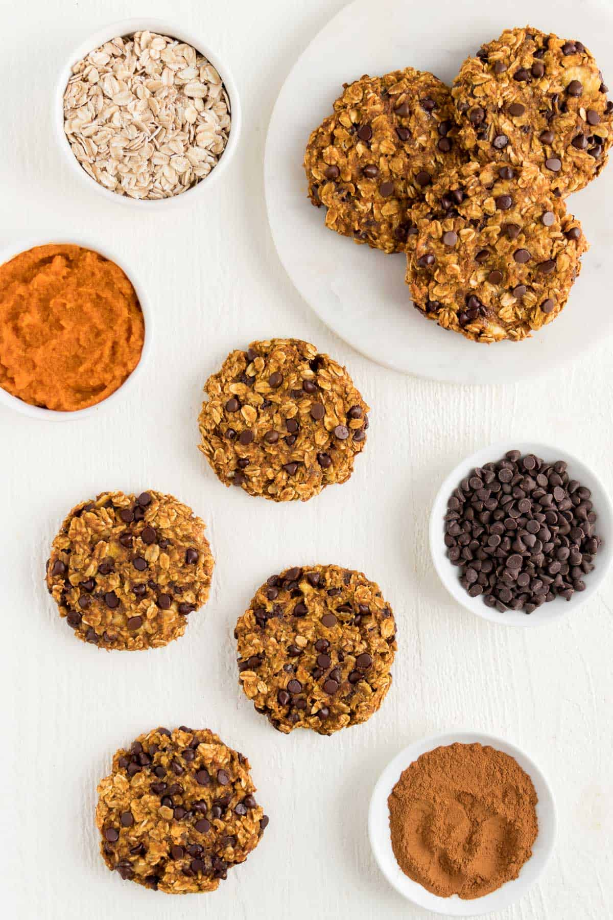 small white bowls containing rolled oats, pumpkin puree, mini chocolate chips, and ground cinnamon surrounded by vegan oatmeal cookies