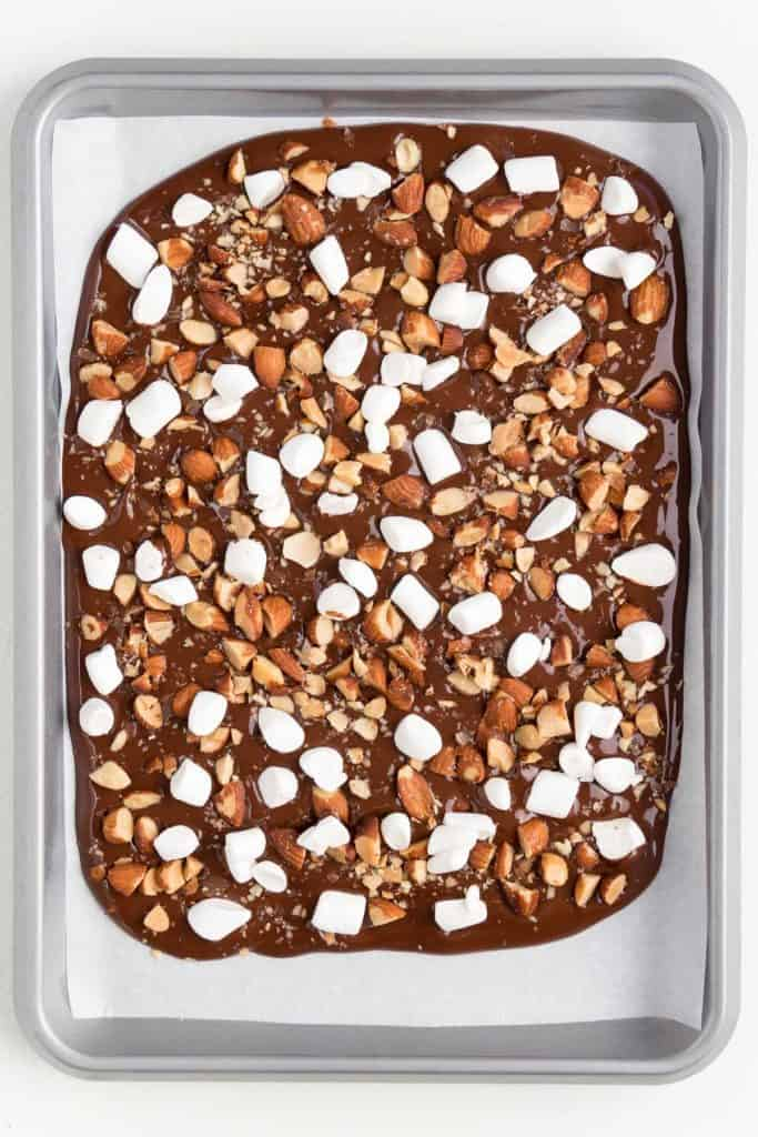 melted chocolate spread across a silver baking sheet topped with chopped almonds and mini marshmallows