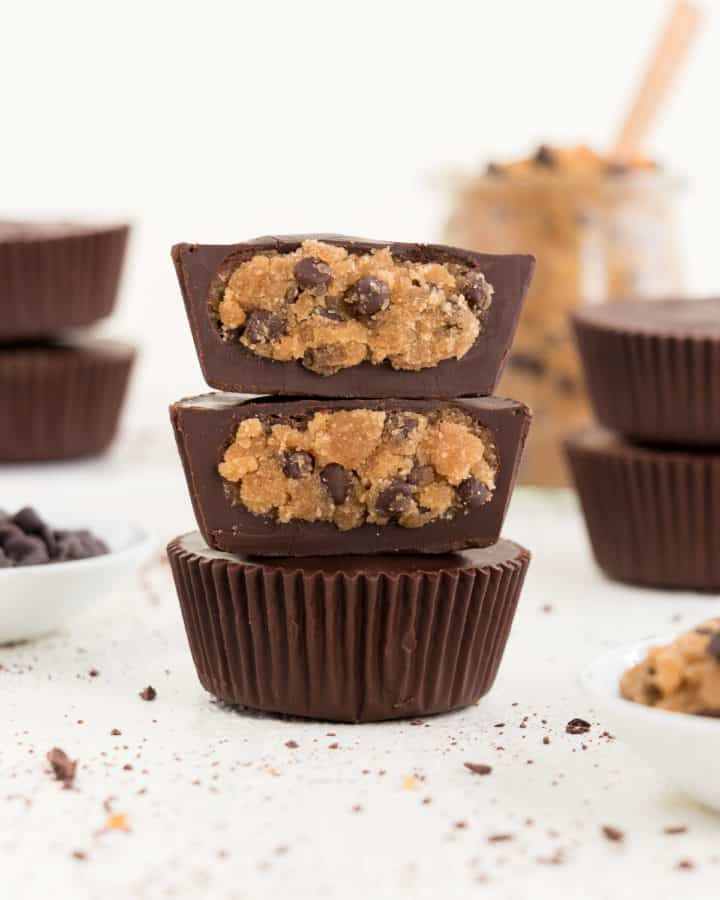 three stacked vegan chocolate chip cookie dough cups surrounded by chocolate chips