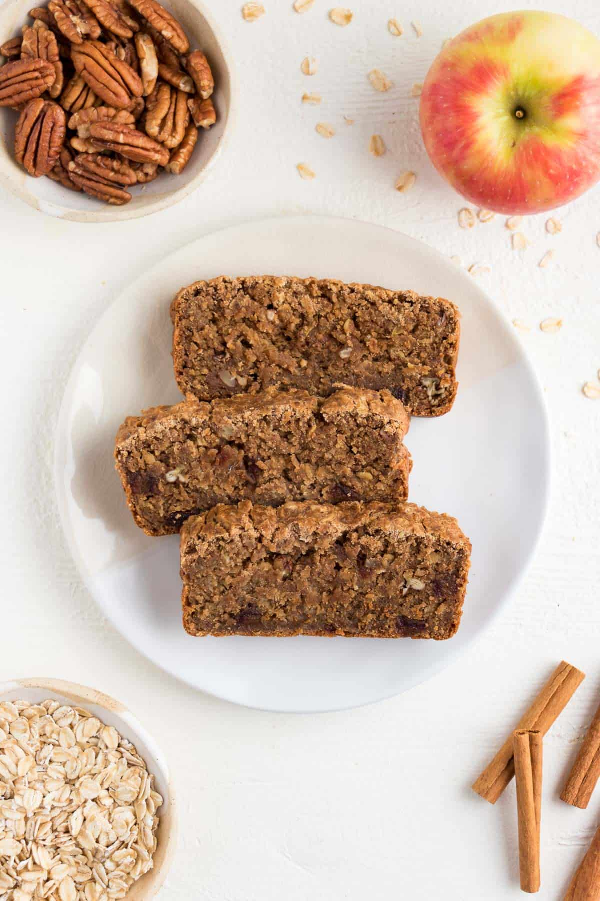 three slices of apple cinnamon bread on a white plate surrounded by cinnamon sticks, pecans, oats, and honeycrisp apple
