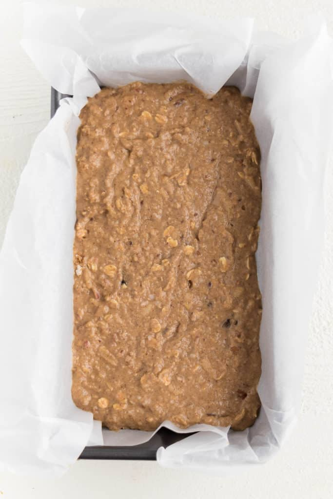 apple bread batter inside a loaf pan lined with white parchment paper