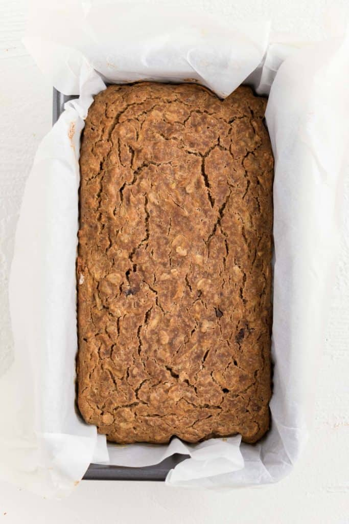 baked apple cinnamon bread inside a metal loaf pan lined with white parchment paper