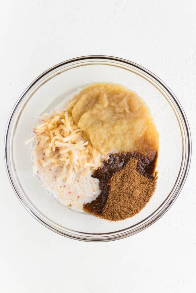 applesauce, coconut sugar, shredded apple, and almond milk inside a large glass pyrex bowl