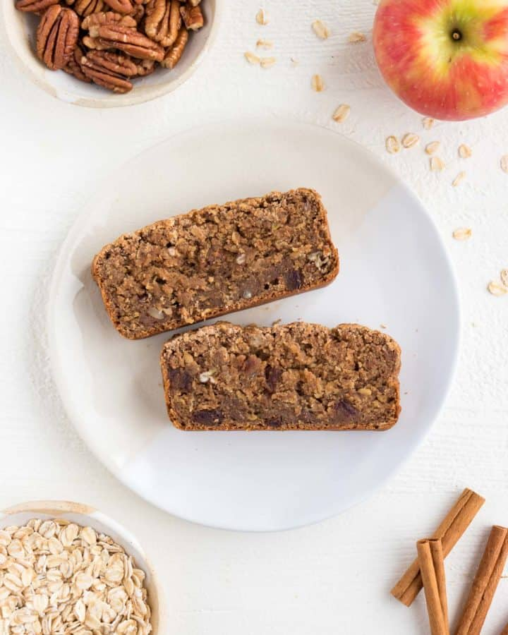 two slices of apple cinnamon bread on a white ceramic plate surrounded by a honeycrisp apple, cinnamon sticks, rolled oats, and pecans