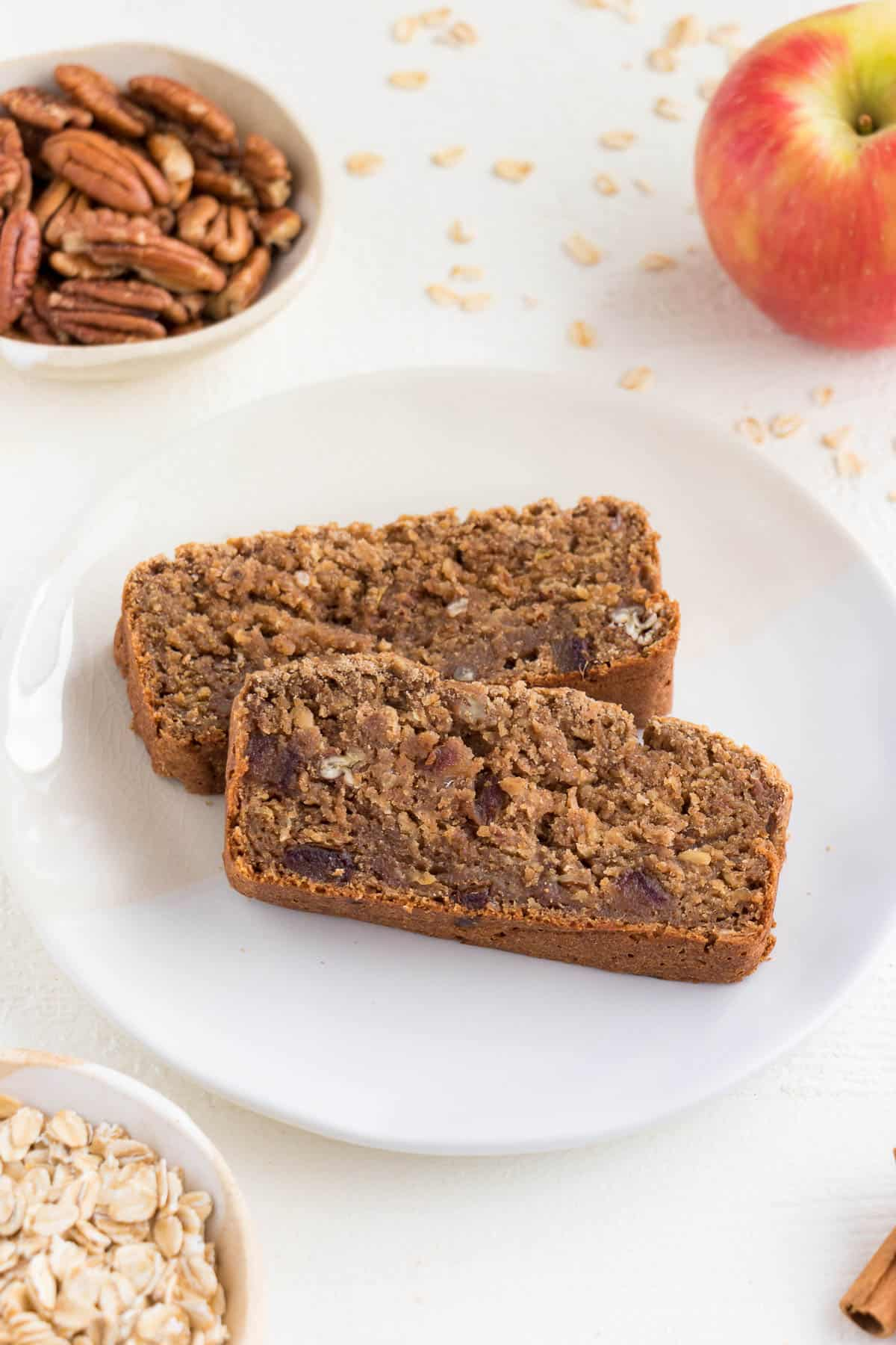 a white plate with two slices of freshly baked apple cinnamon bread surrounded by pecans, apple, cinnamon, and oats