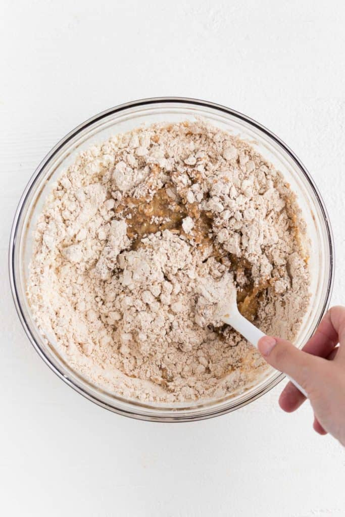 a hand holding a white spatula mixing dry ingredients with wet ingredients in a glass bowl