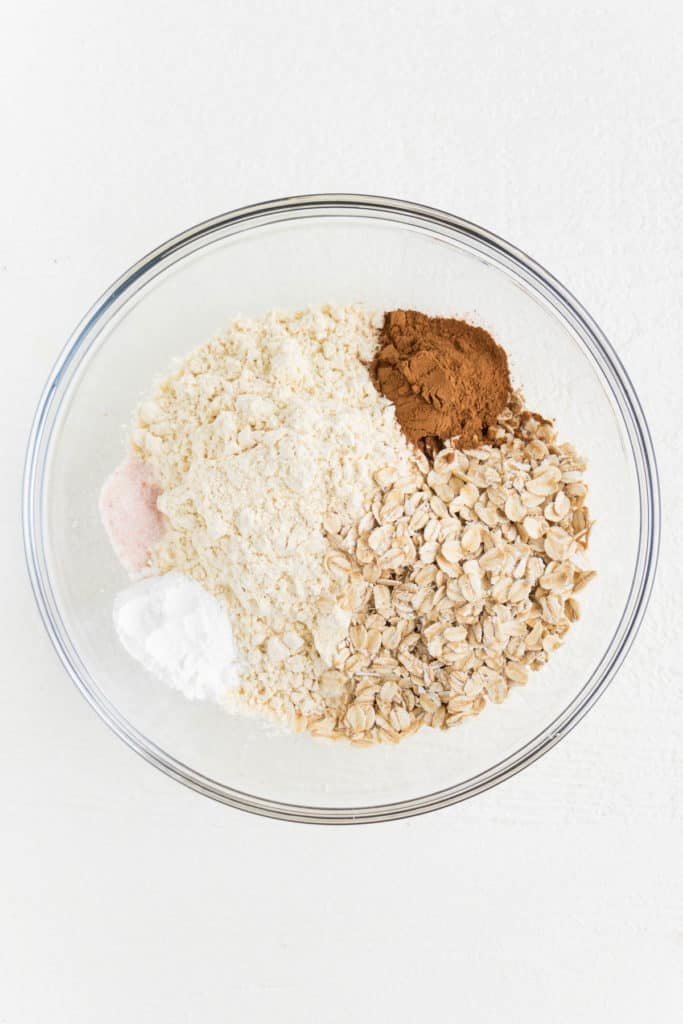 all purpose flour, rolled oats, baking powder, and salt inside a large glass pyrex bowl