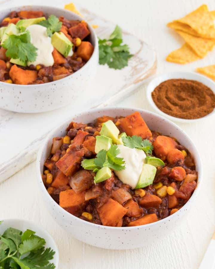 a white ceramic bowl filled with vegan sweet potato black bean chili surrounded by cilantro, tortilla chips, and chili powder