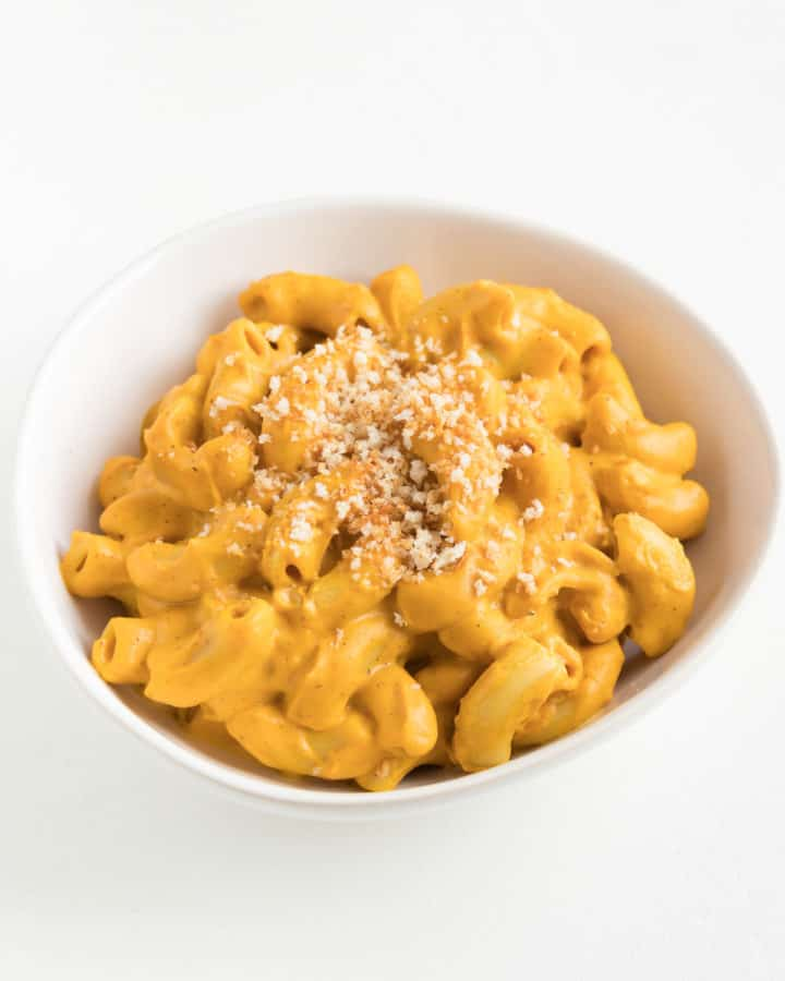 vegan sweet potato mac and cheese topped with toasted breadcrumbs inside a white bowl