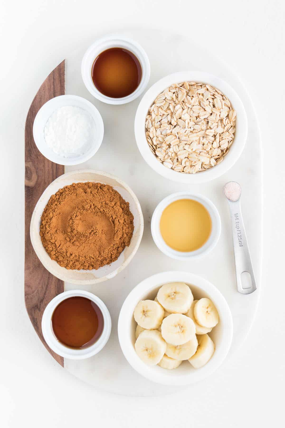 oats, cinnamon, maple syrup, sliced banana, and vanilla extract in small white bowls on a marble cutting board