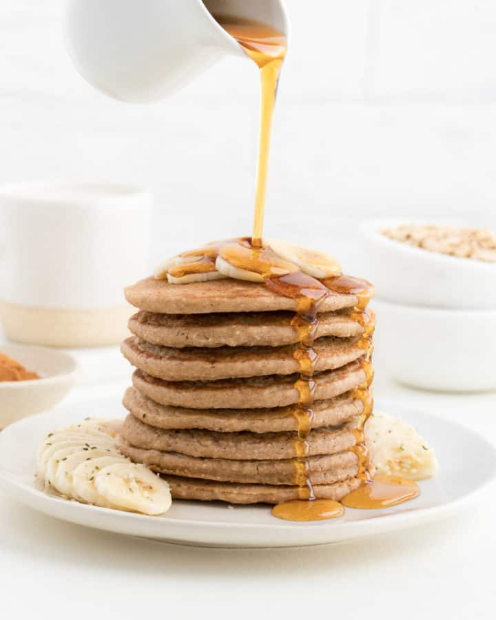 hand pouring maple syrup over a stack of banana pancakes