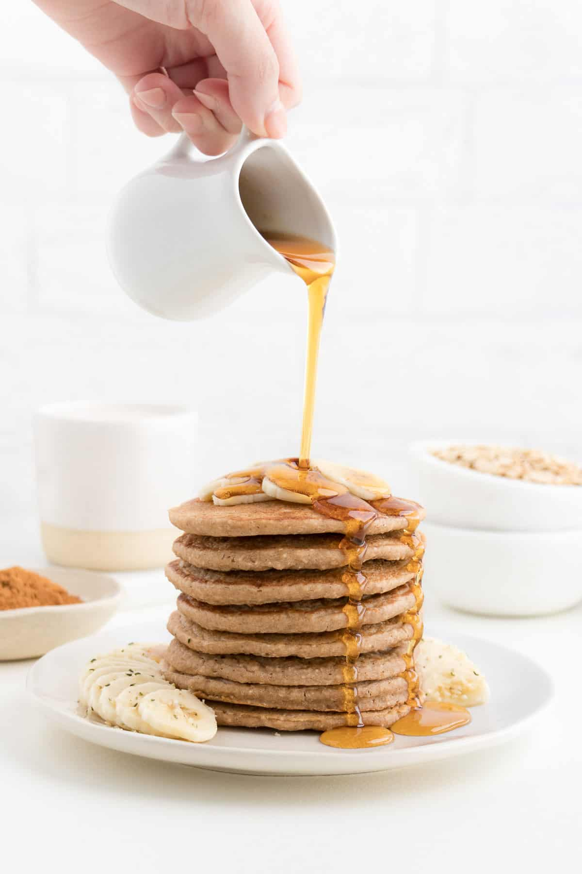 hand pouring maple syrup over a pancake stack topped with banana slices