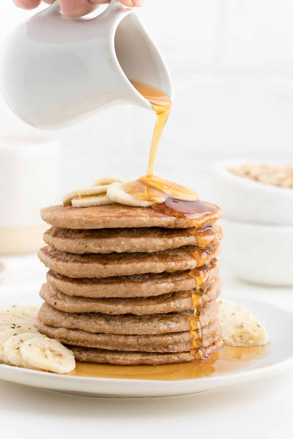 maple syrup being poured over a pancake stack topped with banana slices