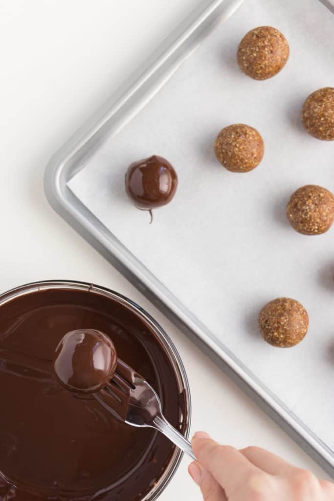metal fork dipping a gingerbread truffle into a glass bowl of melted chocolate, next to a baking sheet with gingerbread truffles
