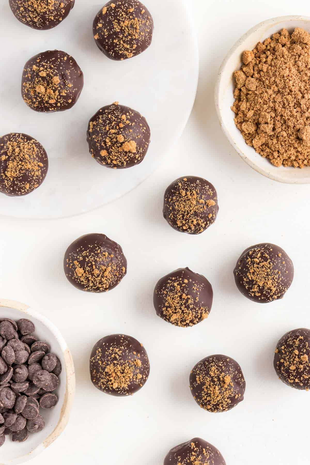chocolate gingerbread truffles scattered across a white surface beside a small ceramic bowl filled with chocolate chips and crumbled gingersnap cookies
