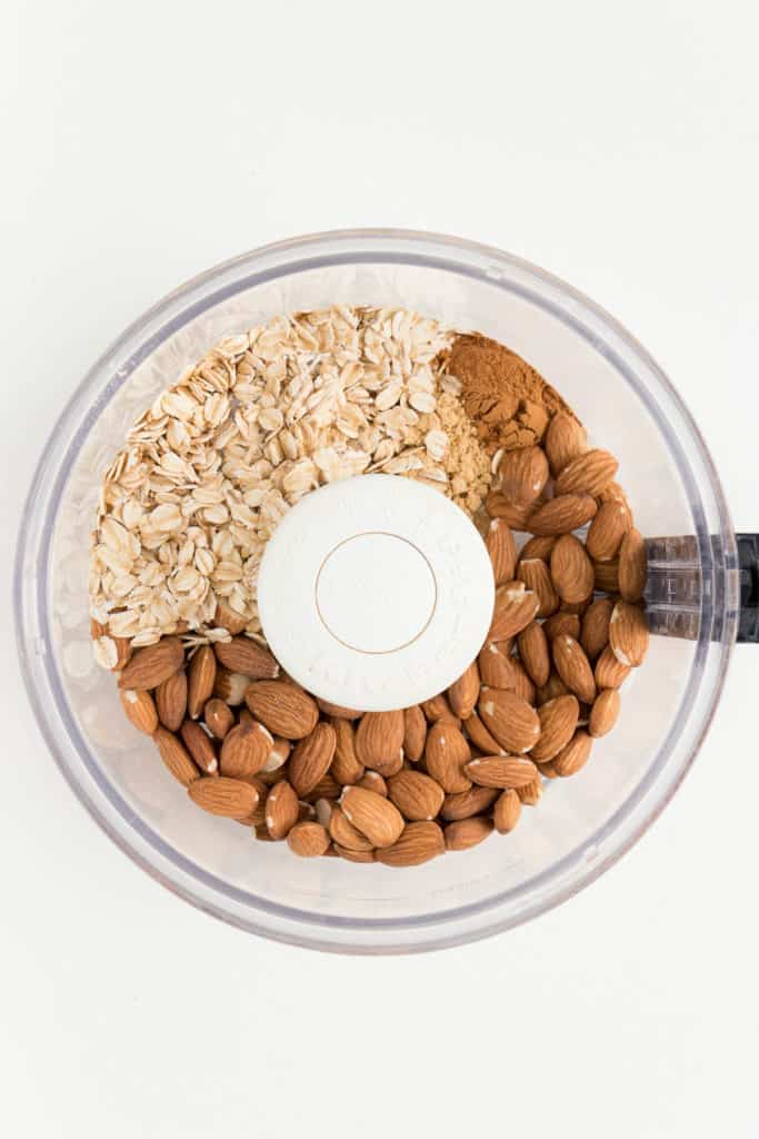 rolled oats, almonds, cinnamon, and ginger inside a food processor