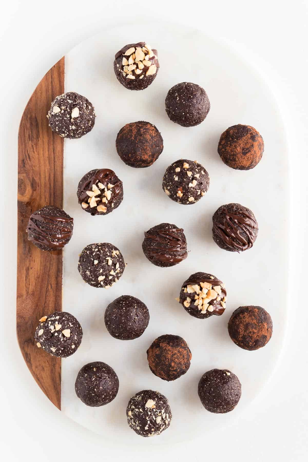 chocolate peanut butter bliss balls on top of a white marble and wood cutting board