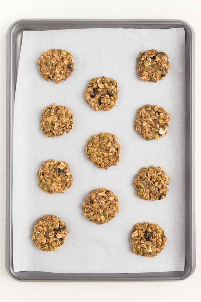 metal baking sheet lined with white parchment paper and superfood breakfast cookies on top