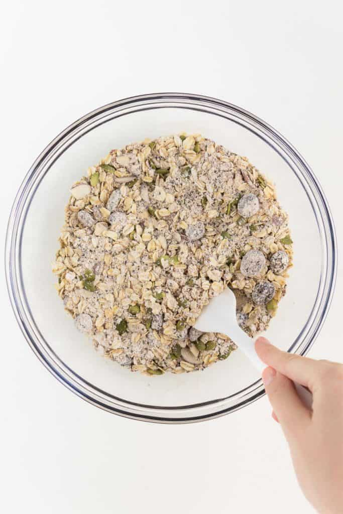 hand holding a white spatula mixing oat flour and superfoods in a glass bowl
