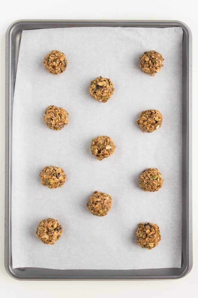 11 balls of superfood cookie dough on a metal baking sheet lined with white parchment paper