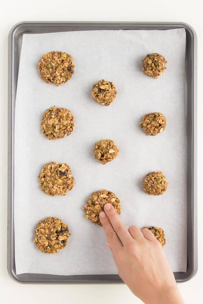 hand pressing balls of superfood cookie dough into cookies on a metal baking sheet