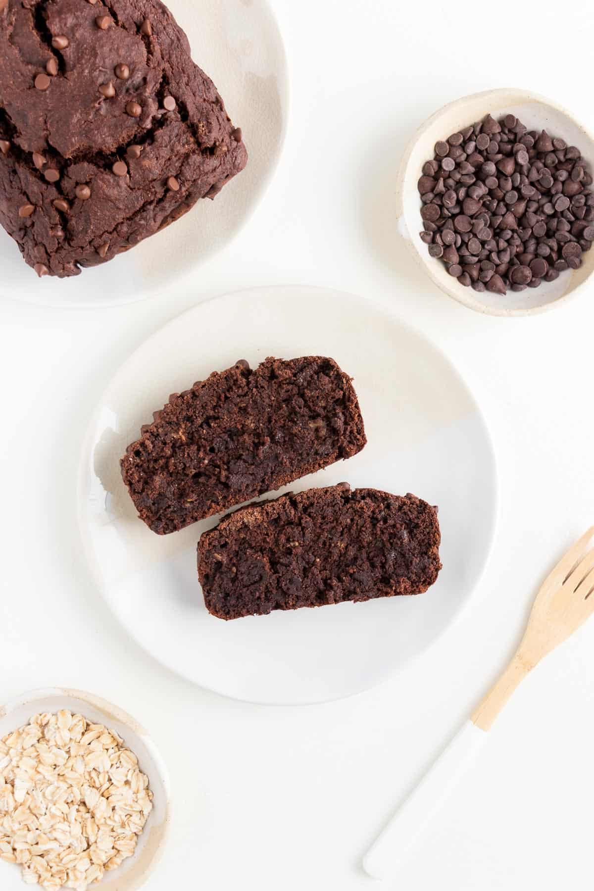 two slices of vegan gluten-free chocolate banana bread on a white plate surrounded by a small bowl of chocolate chips and a small bowl of rolled oats