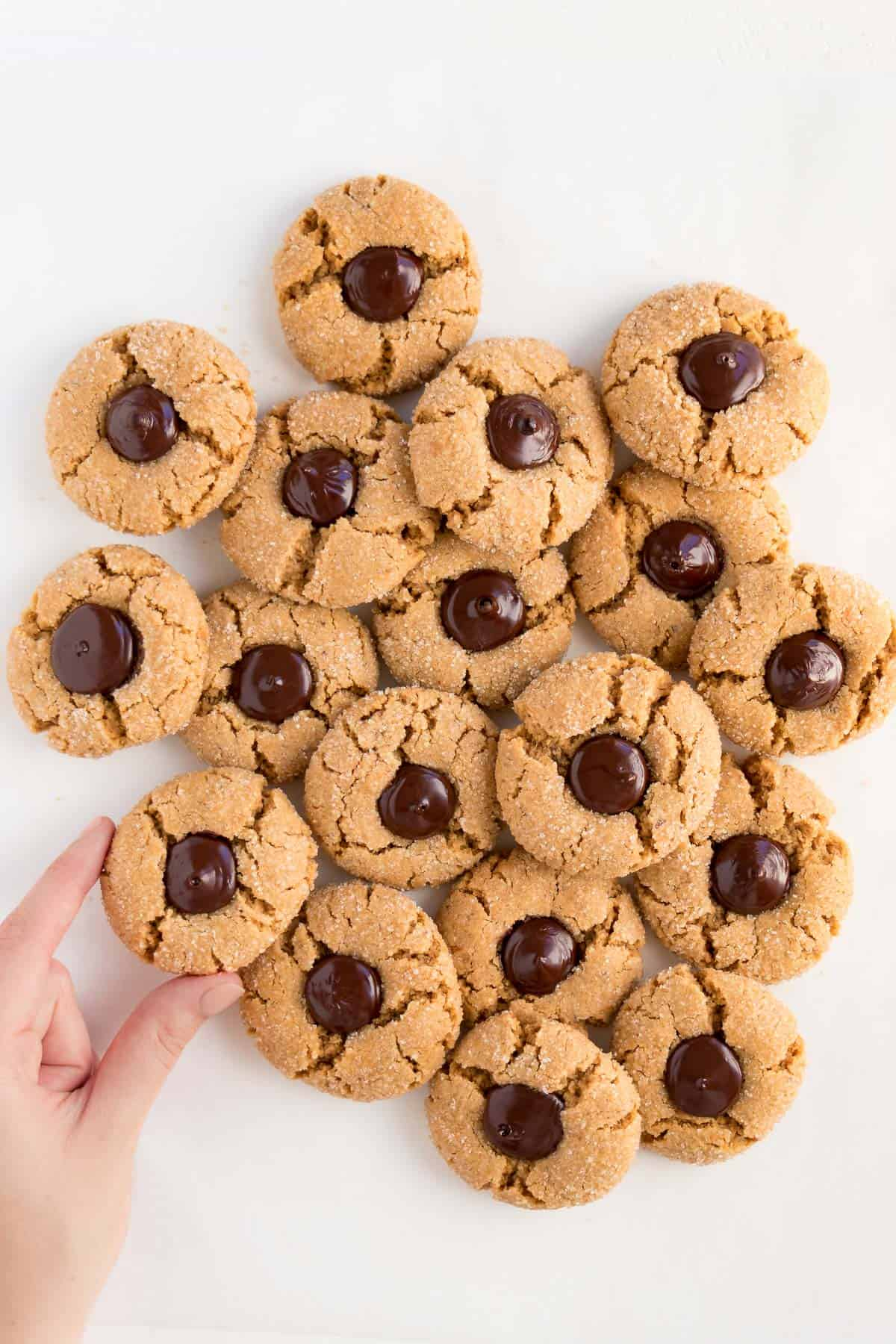 a hand grabbing a pile of vegan peanut butter blossoms on a white surface
