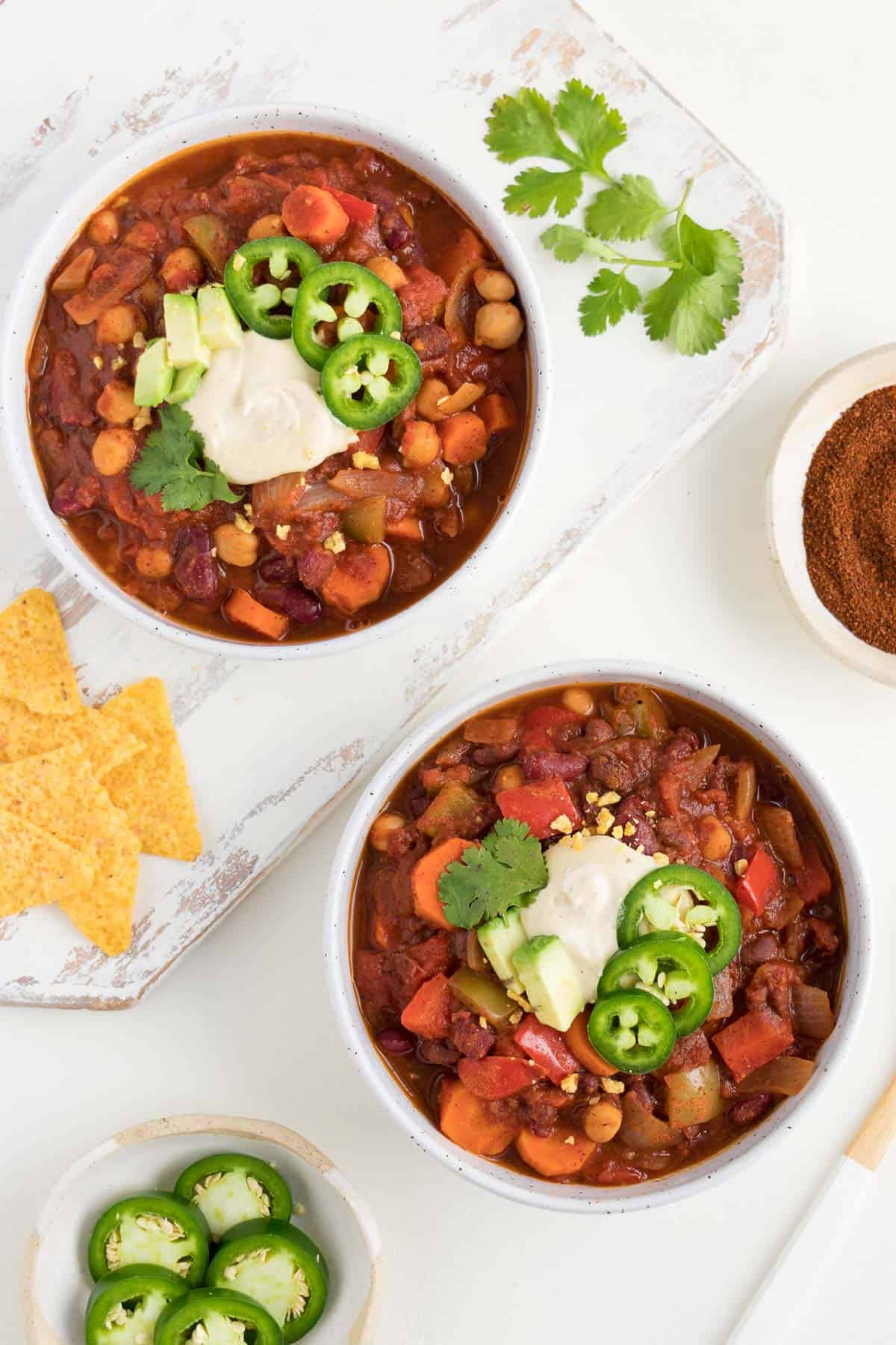 two bowls of chili on a white surface alongside corn tortilla chips, chili powder, cilantro, and sliced jalapeño peppers