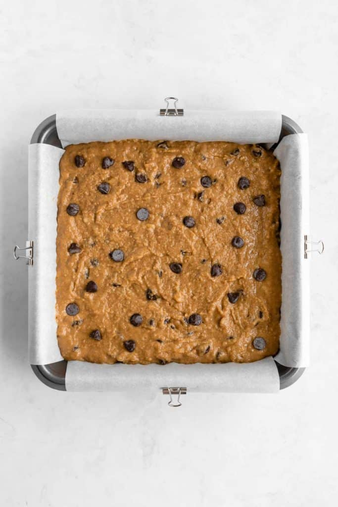 a hand holding a white spatula spreading chocolate chip banana blondie batter inside a square baking dish
