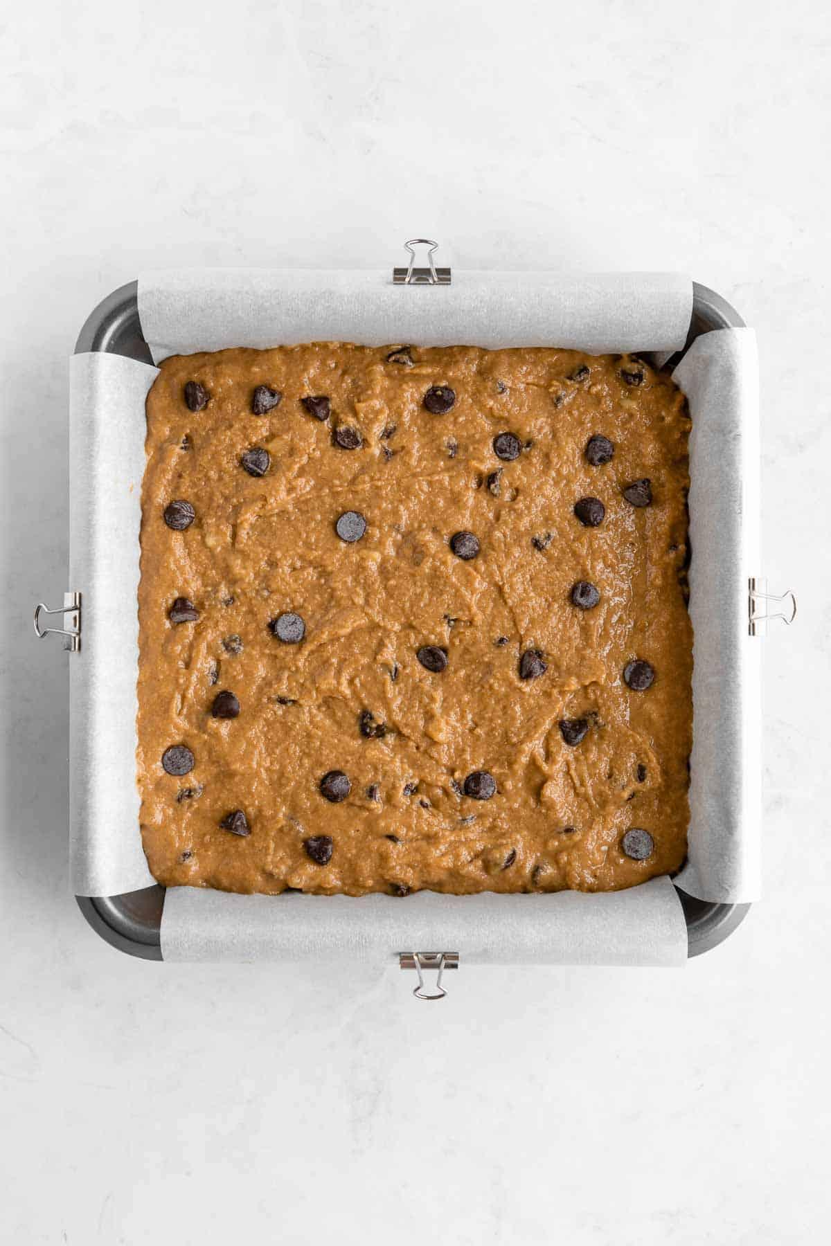 vegan gluten-free chocolate chip banana blondies batter in a square baking dish