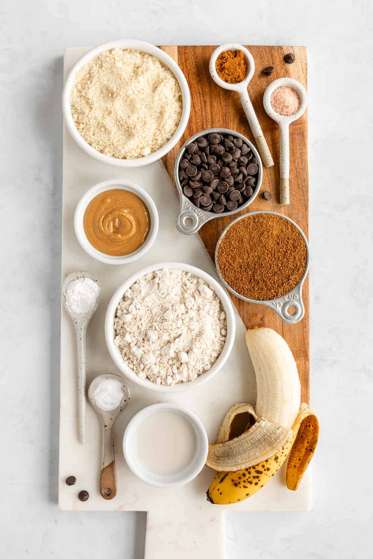 a marble and wood serving board topped with bowls of almond flour, oat flour, coconut sugar, banana, chocolate chips, peanut butter, and almond milk