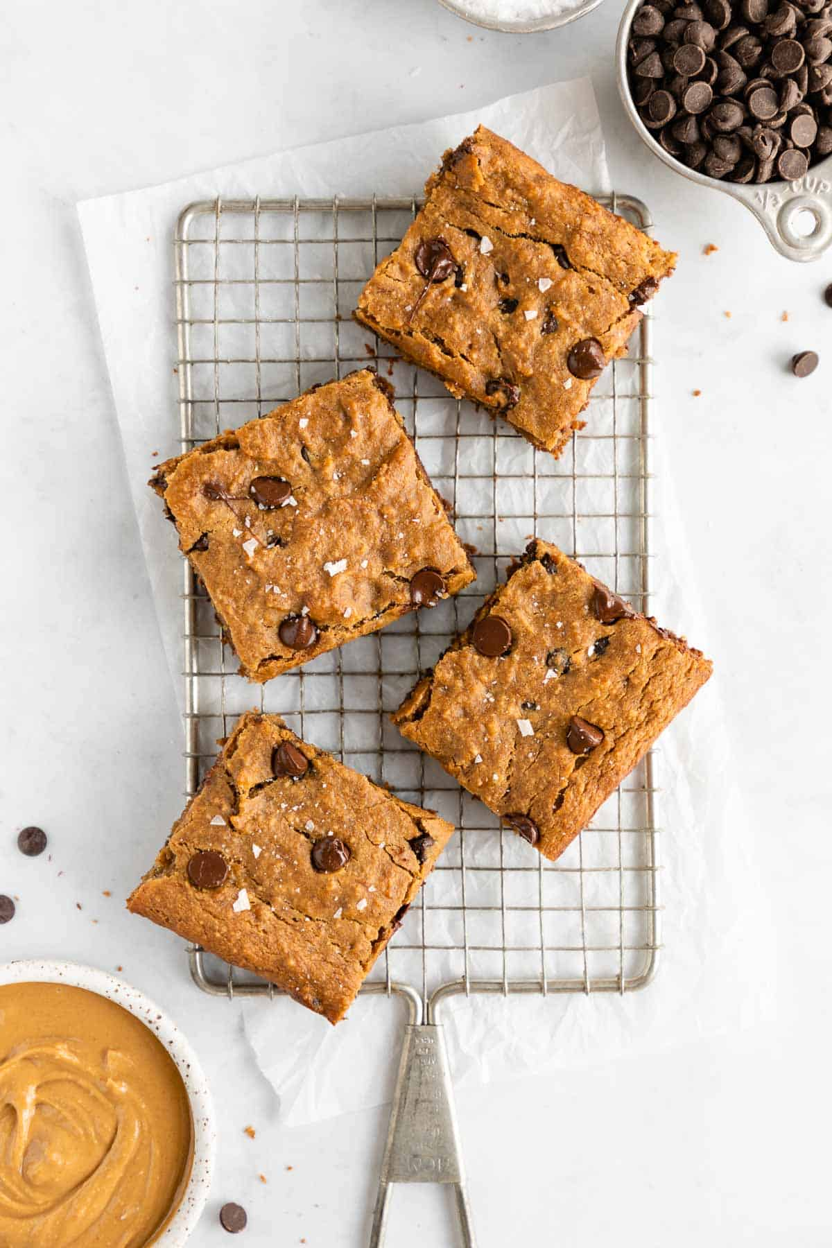 chocolate chip banana blondie bar on top of a square white plate surrounded by chocolate chips, almond milk, peanut butter, and a wooden fork
