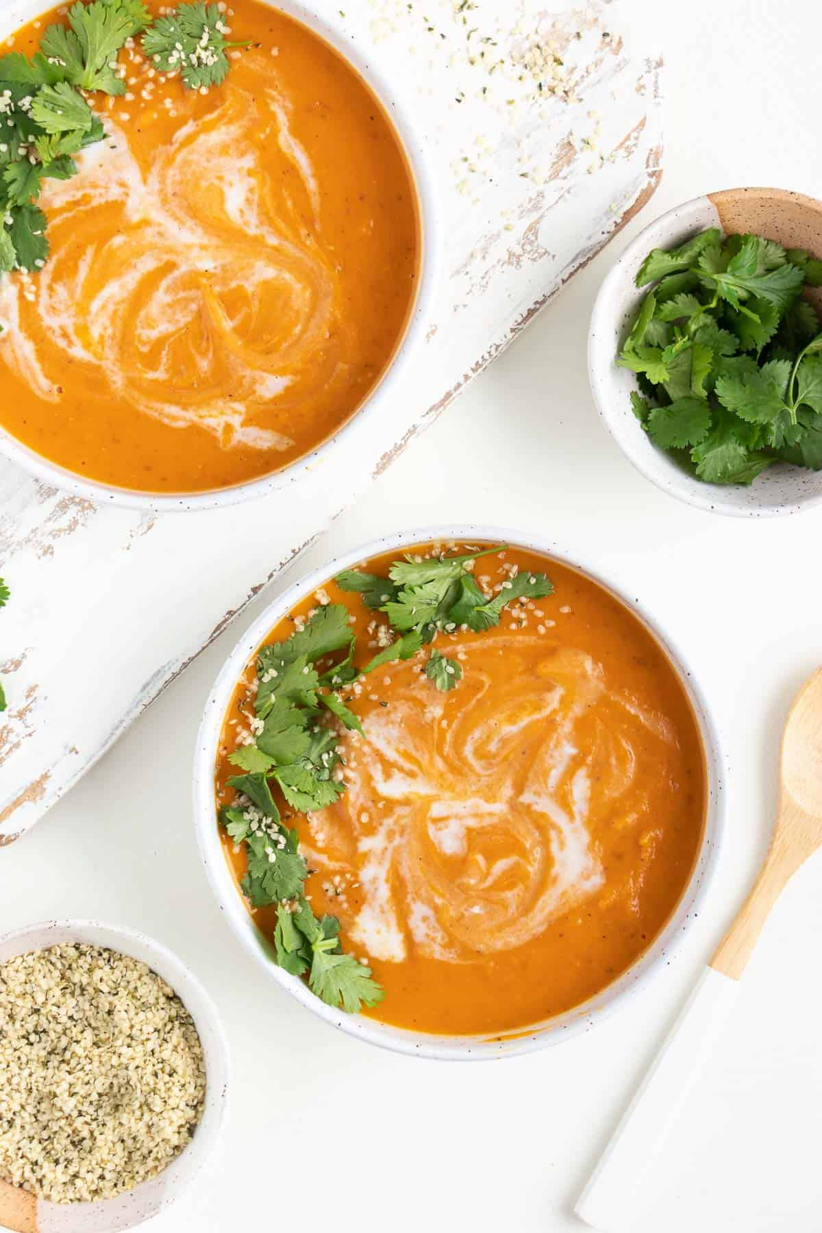 sweet potato soup inside two white bowls beside wooden spoon, a bowl of hemp seeds, and a bowl of cilantro