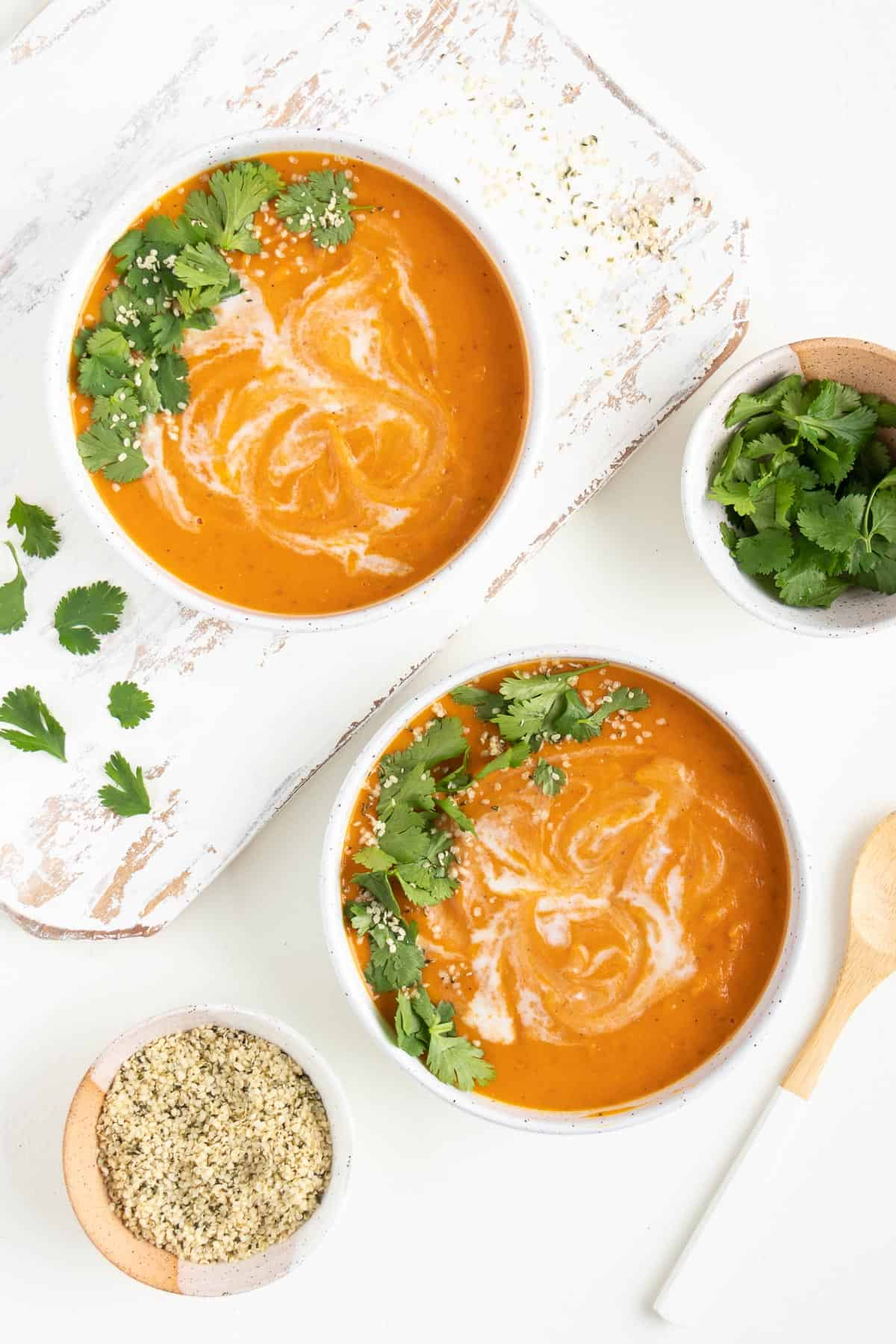 orange soup in two white bowls next to a wooden spoon, a bowl of hemp seeds, and a bowl of cilantro
