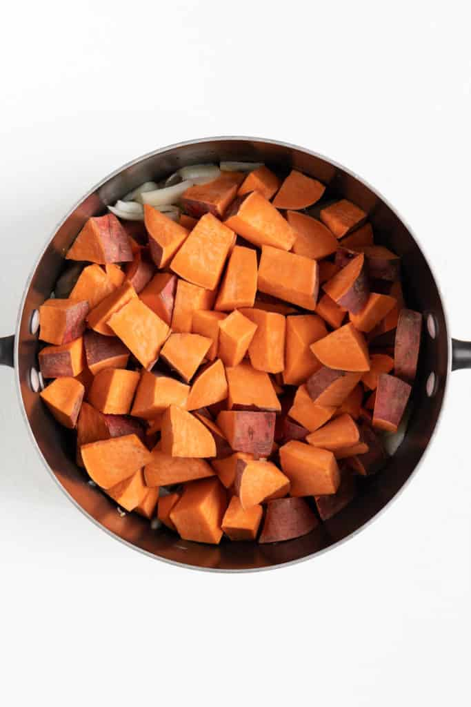 cubed sweet potatoes inside a black sauce pot