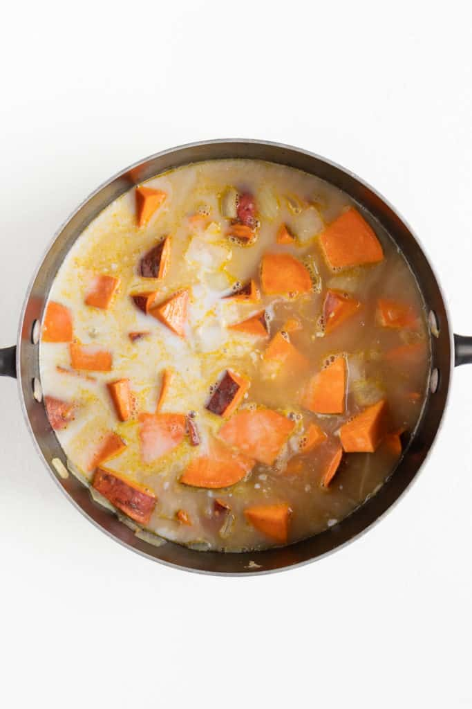 vegetable broth, coconut milk, and cubed sweet potatoes inside a black sauce pot