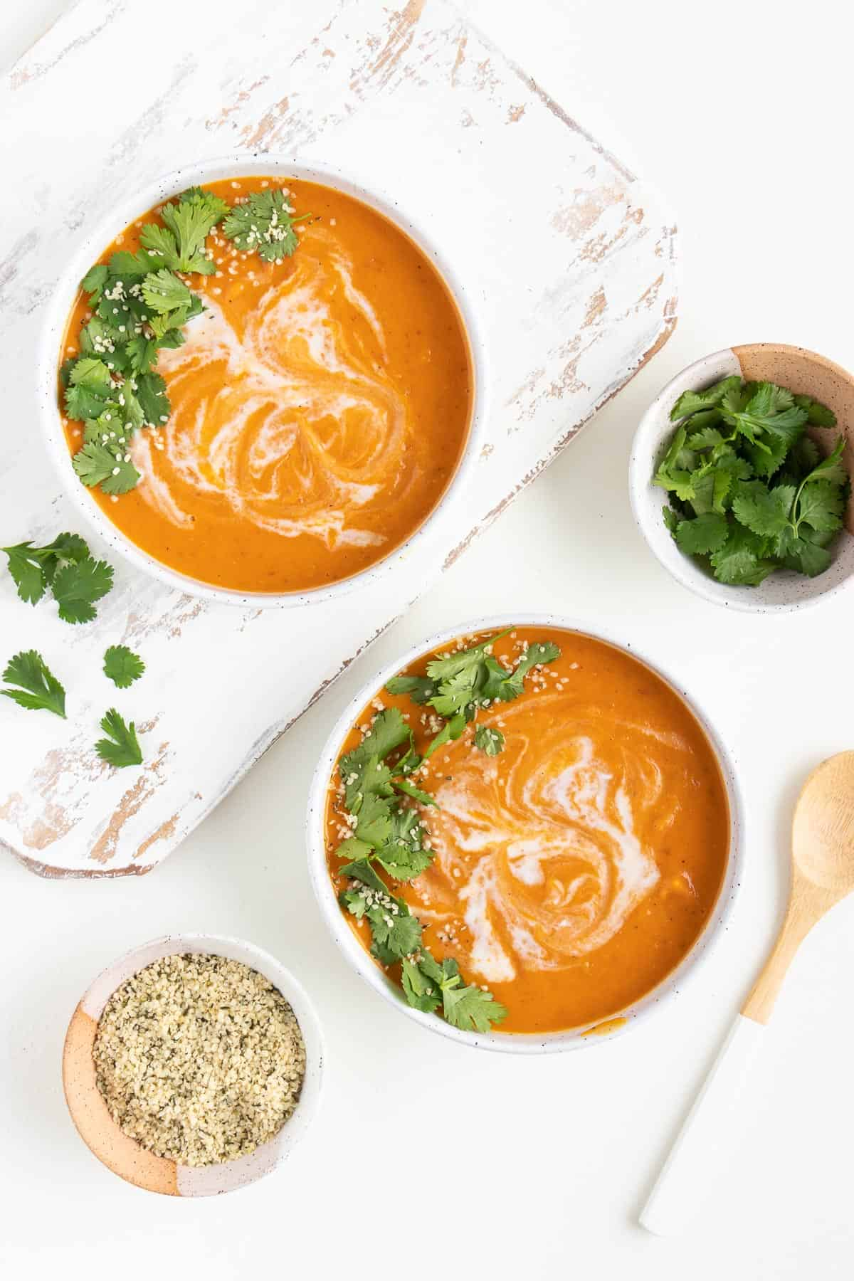 two bowls of creamy vegan sweet potato soup next to small bowls with cilantro and hemp seeds inside