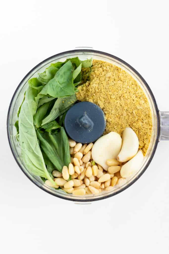 basil, nutritional yeast, garlic cloves, and pine nuts in a food processor