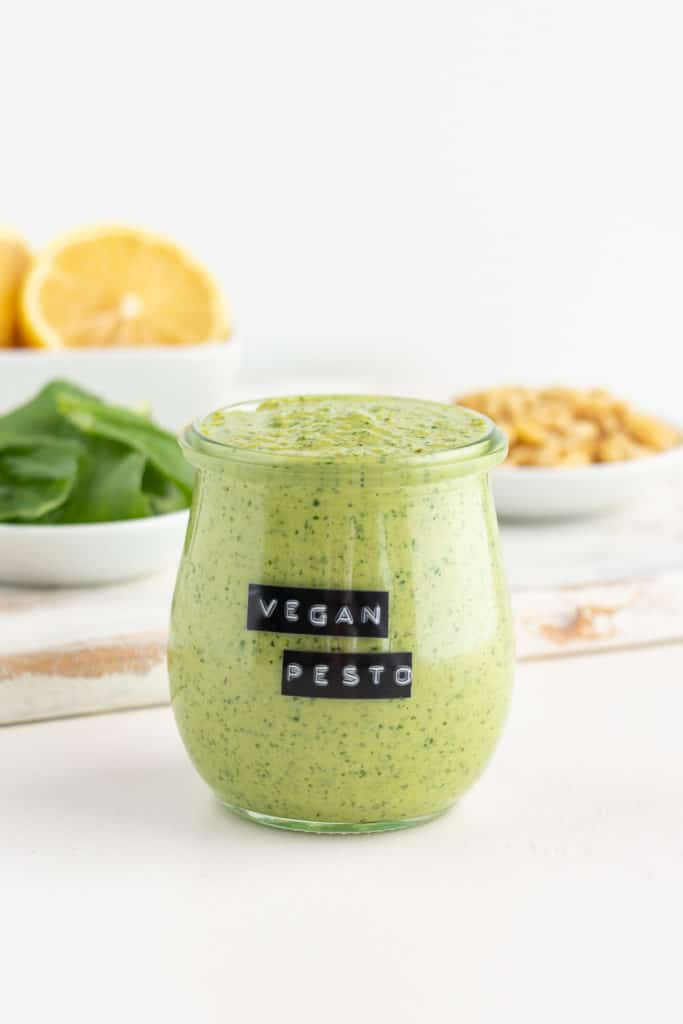 vegan pesto inside a glass jar surrounded by lemons, basil, and pine nuts
