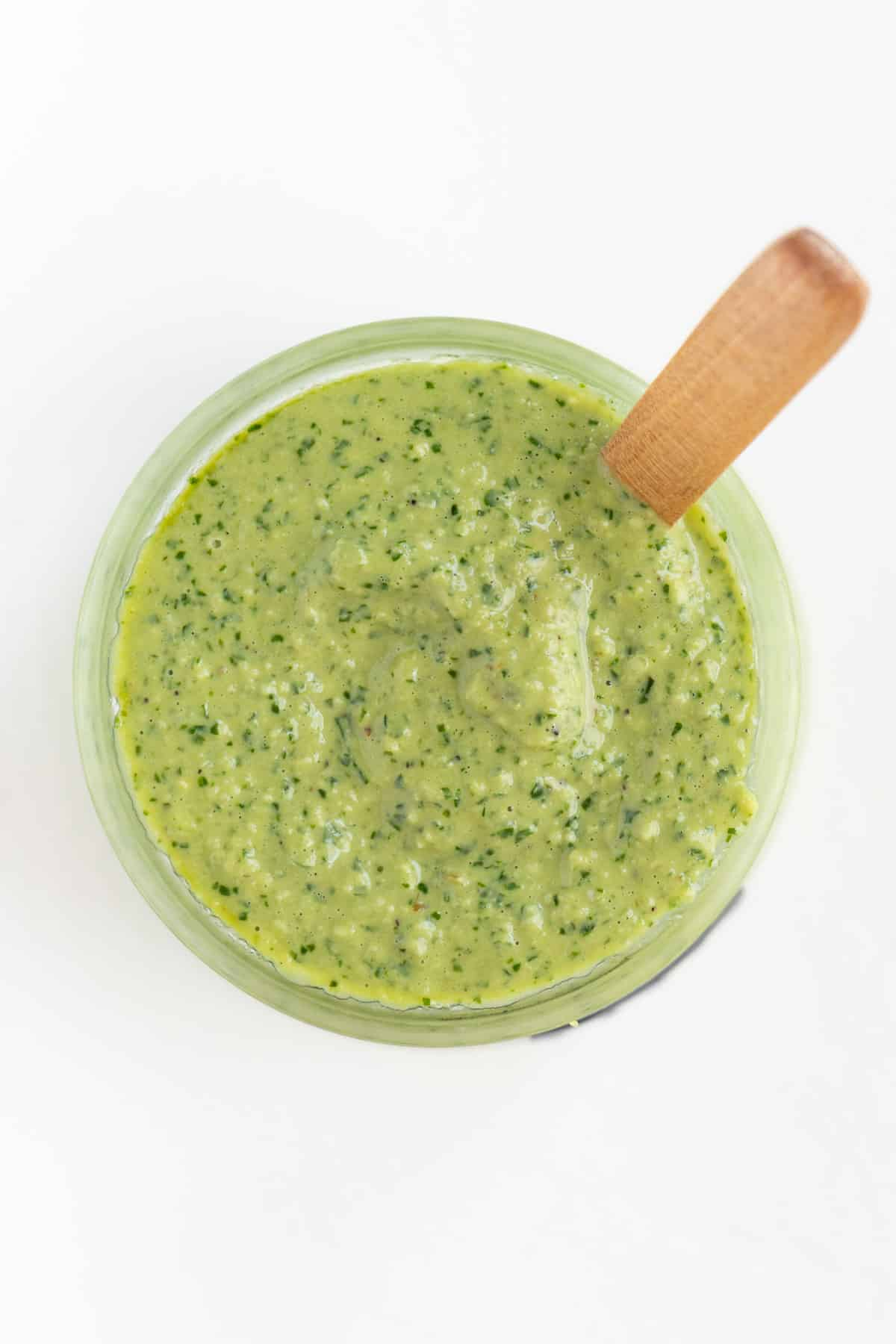 green pesto sauce inside a glass jar with a wooden spoon sticking out of it