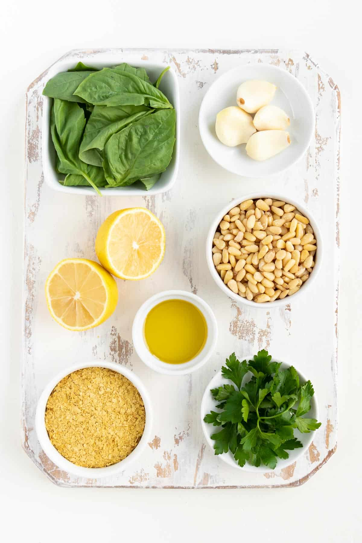 a distressed white wooden cutting board topped with small bowls of basil leaves, garlic cloves, pine nuts, lemon juice, olive oil, nutritional yeast, and parsley