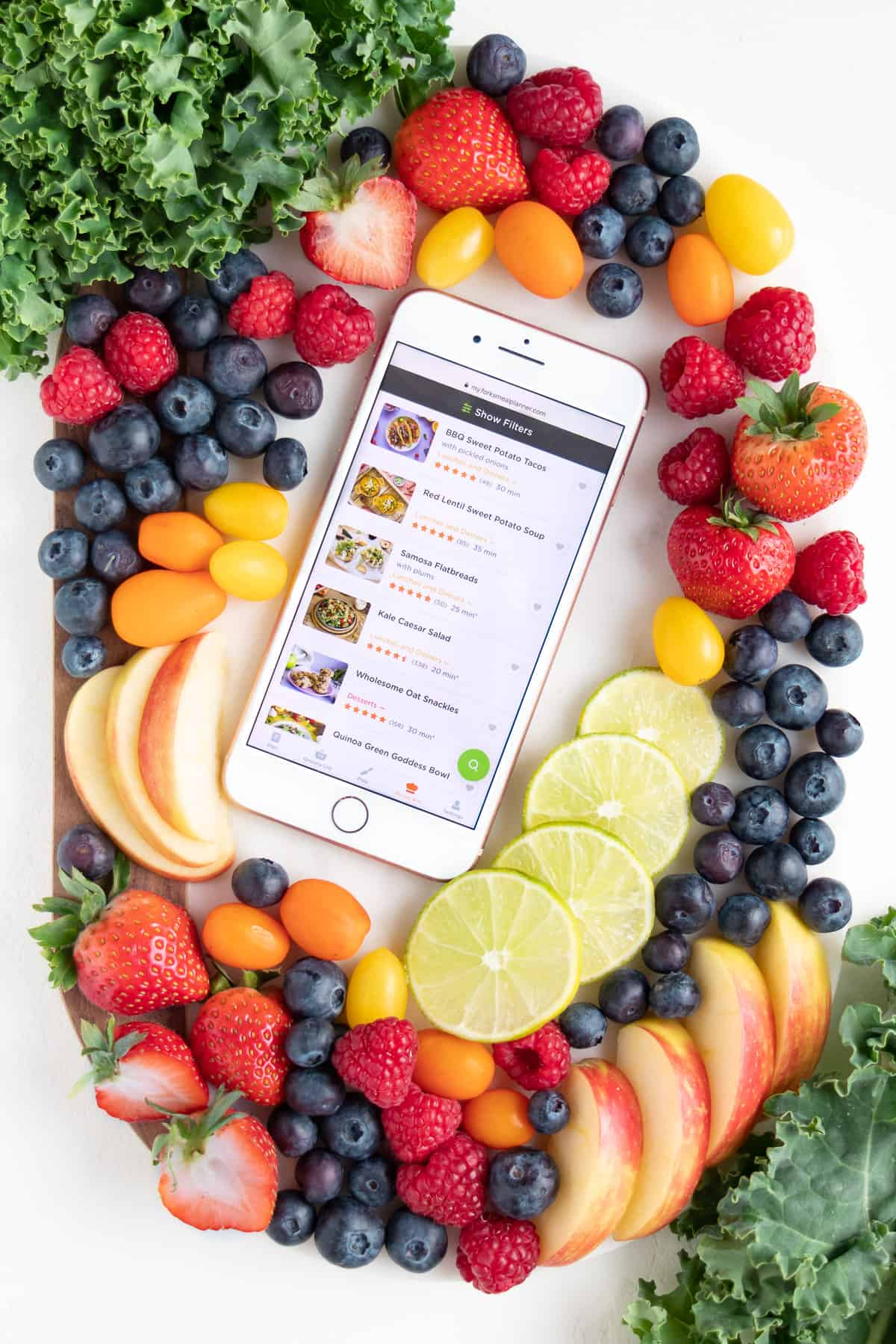 an iphone showing the forks over knives meal planner surrounded by kale, berries, lime, apple wedges, and cherry tomatoes