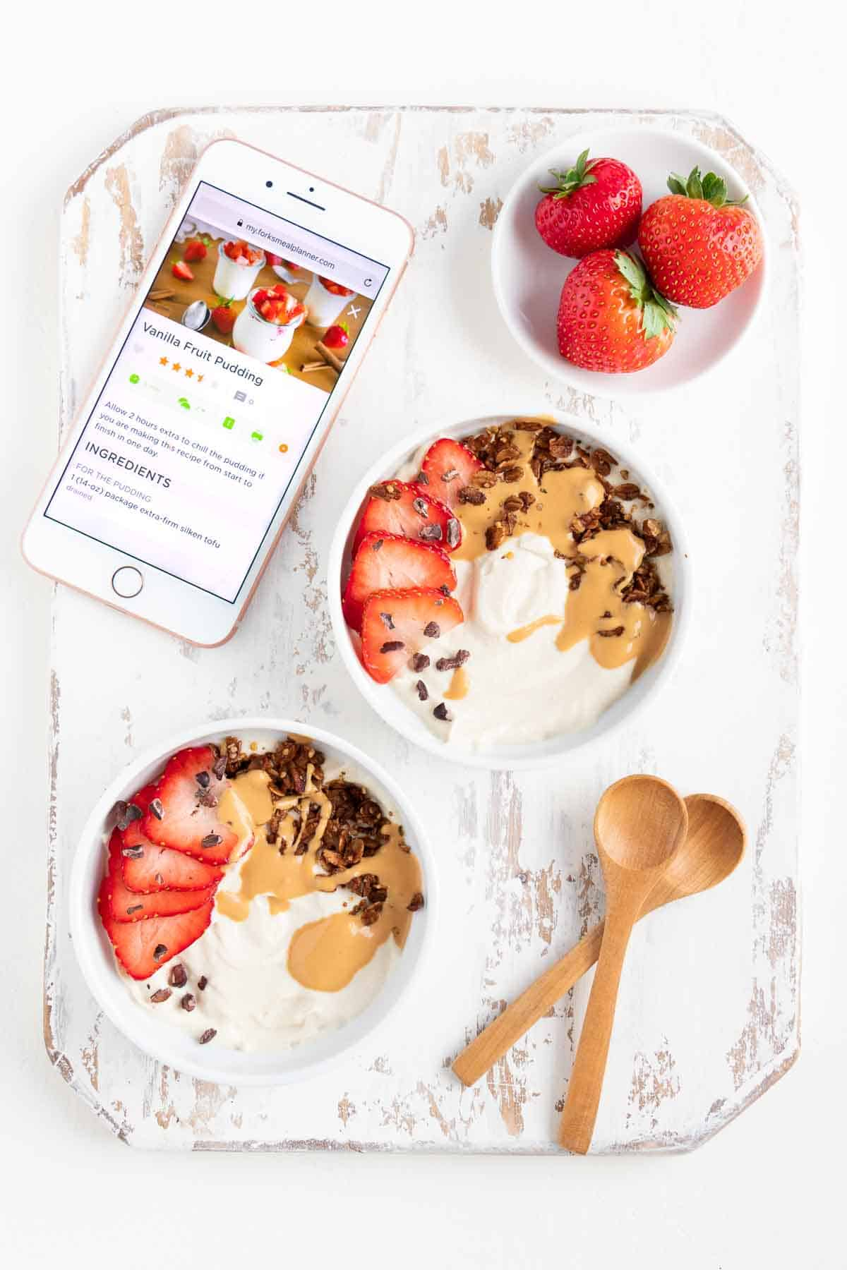two white bowls of vanilla pudding on top of a distressed wooden cutting board with two wooden spoons, strawberries, and an iphone