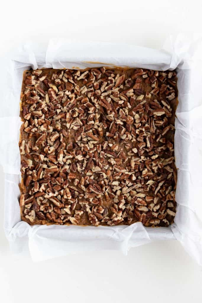 crushed pecans spread across the base of a square baking dish