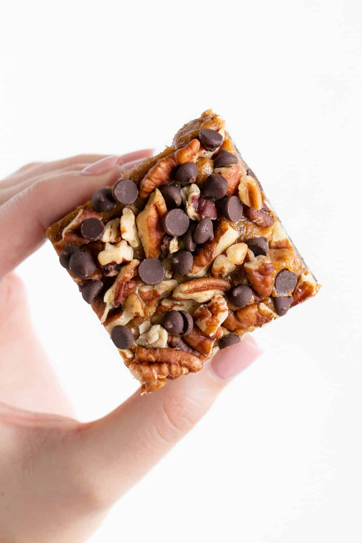hand holding a no bake raw turtle brownie
