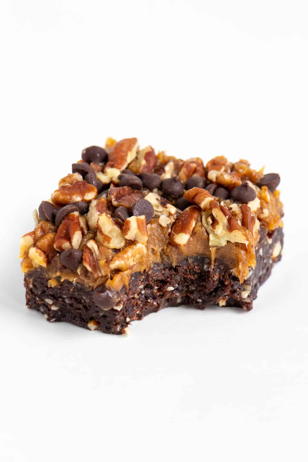 raw vegan no bake turtle brownie with a bite taken out of it