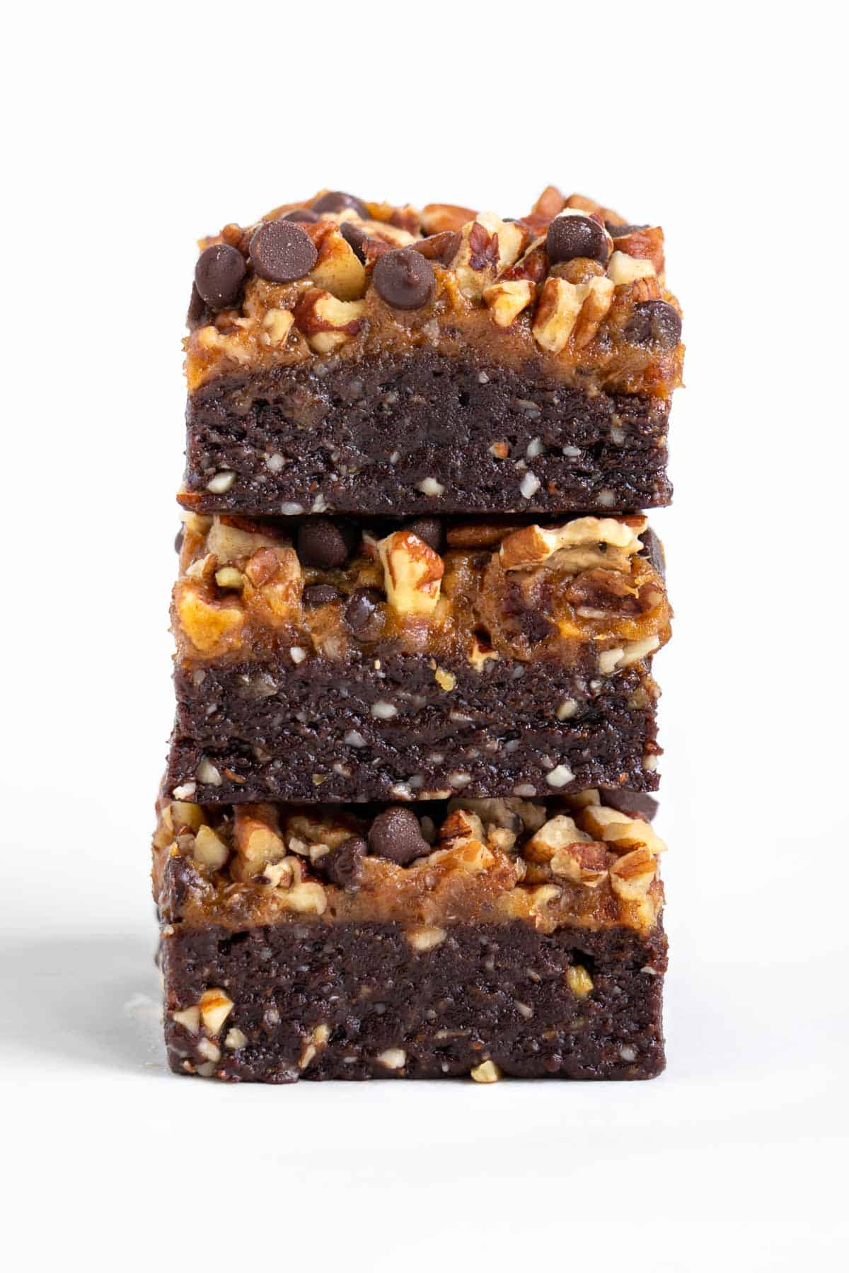 three no bake raw turtle brownies stacked on top of each other